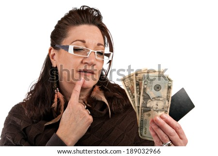 Middle aged woman carefully trying to decide between using old fashioned cash or a plastic credit card.