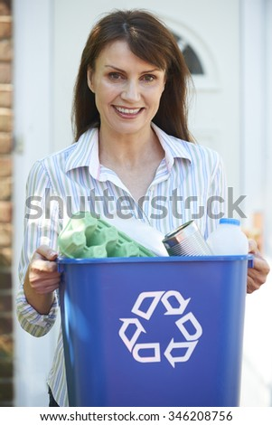 Middle Aged Woman Carrying Recycling Bin