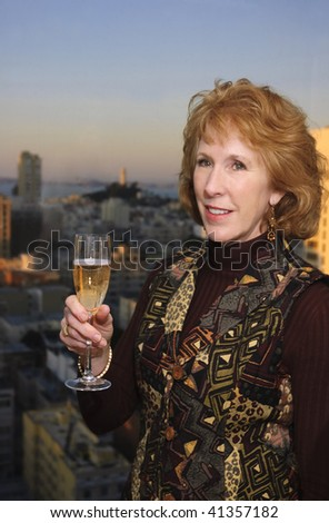 middle aged Woman celebrating with champagne in san Francisco with Coit tower in the background - stock photo
