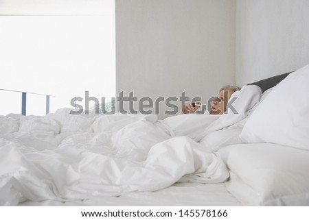 Middle aged woman checking her body temperature with thermometer in bed - stock photo