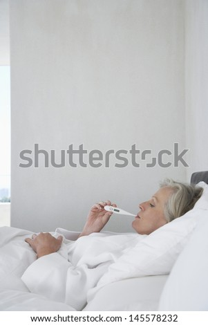 Middle aged woman checking her body temperature with thermometer in bed