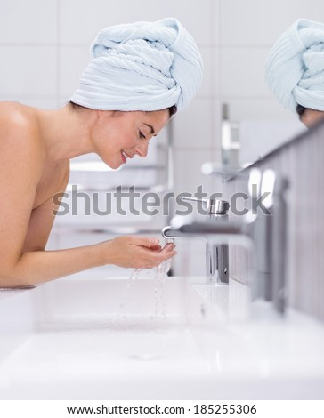 middle aged woman cleaning her sking over the sink - stock photo
