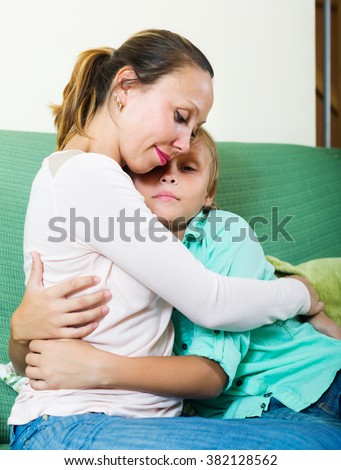 middle-aged woman comforting sad son at home