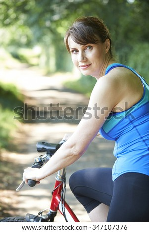 Middle Aged Woman Cycling Along Country Lane