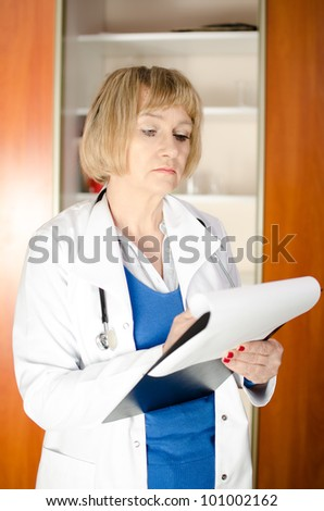Middle aged woman doctor taking notes in clipboard - stock photo