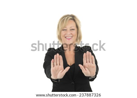 Middle aged woman doing a stop gesture with both hands against a white background - stock photo