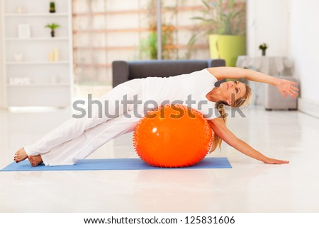 middle aged woman doing fitness on exercise ball at home - stock photo