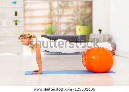 middle aged woman doing push ups with exercise ball - stock photo