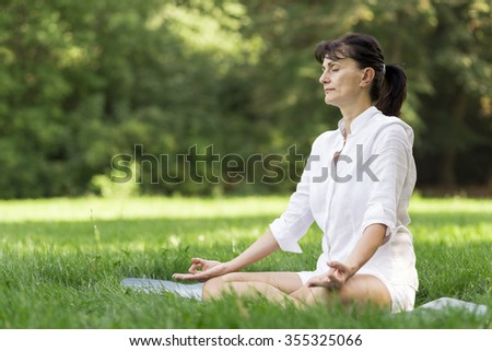 Middle aged woman doing yoga early in the morning in a park - stock photo