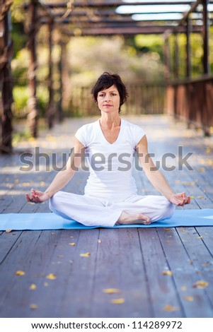 middle aged woman doing yoga meditation on deck - stock photo