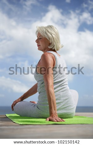 Middle-aged woman doing yoga outdoors - stock photo