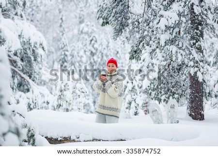 Middle-aged woman having a winter picnic in snowy forest