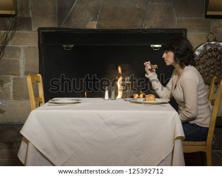 Middle aged woman having dinner without companion - stock photo