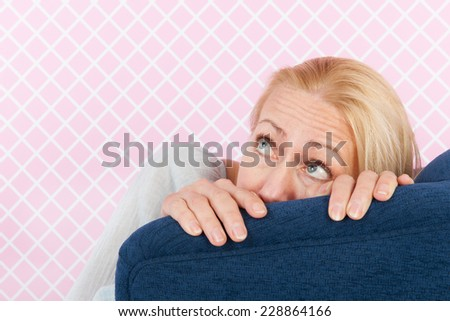 middle aged woman having fear in the living room - stock photo