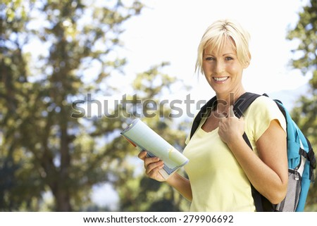 Middle Aged Woman Hiking Through Countryside - stock photo