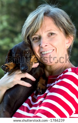 Middle-aged woman holding a dog - stock photo