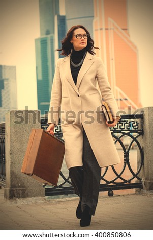 middle-aged woman in a bright coat and with a wooden case and books. instagram image filter retro style