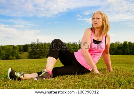 Middle-aged woman in her 40s stretching for exercise outdoors - stock photo