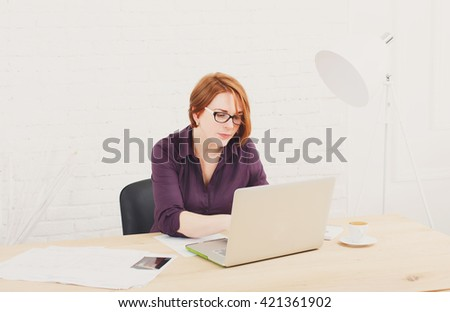 Middle-aged Woman in the office. Female architect using laptop computer and smartphone. Office worker. Redhead caucasian woman in protective glasses with computer. High-key, soft tone.  - stock photo