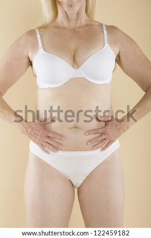 Middle aged woman in white lingerie standing with hands on her belly