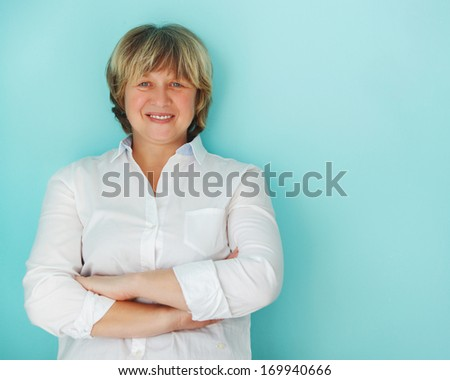Middle aged woman looking at camera with happy smile - stock photo
