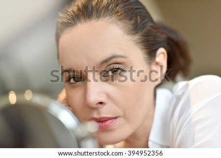 Middle-aged woman looking at mirror - stock photo