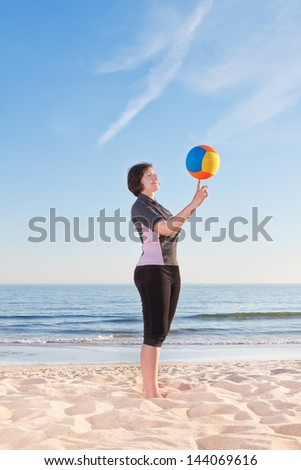 Middle-aged woman on the beach with a volleyball ball playing. Close-up. - stock photo