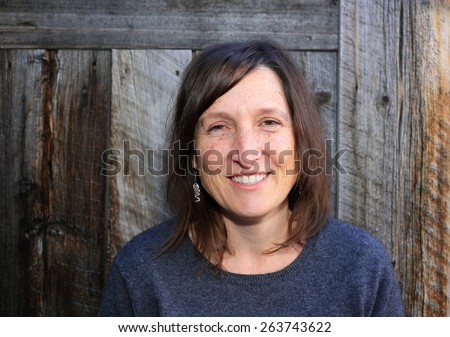 Middle aged woman portrait with a rustic wood background. - stock photo