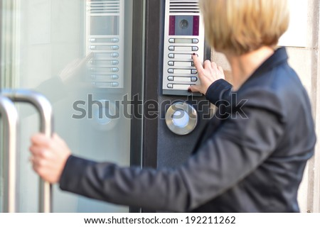 Middle aged woman pushing button of intercom - stock photo