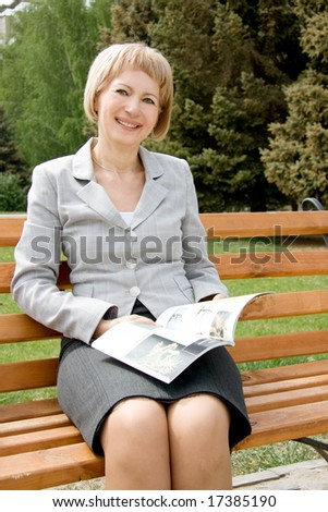 Middle-aged woman reading in a park - stock photo