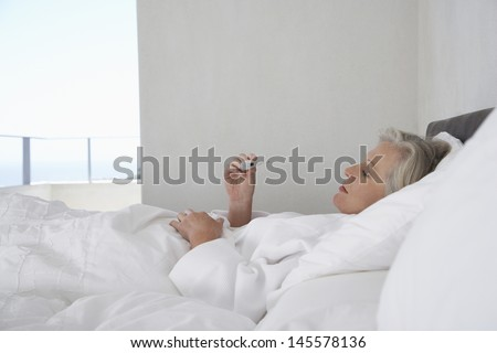 Middle aged woman reading temperature from thermometer in bed - stock photo