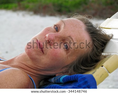 Middle-Aged Woman Relaxing and Tanning on Beach - stock photo