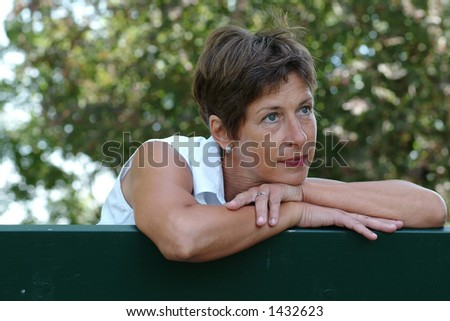 Middle aged woman sitting in a park - stock photo