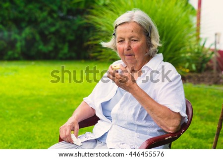 Middle-aged woman sitting in the yard. - stock photo