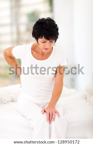 middle aged woman sitting on bed having back pain - stock photo