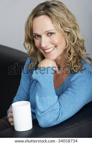 Middle Aged Woman Sitting On Sofa