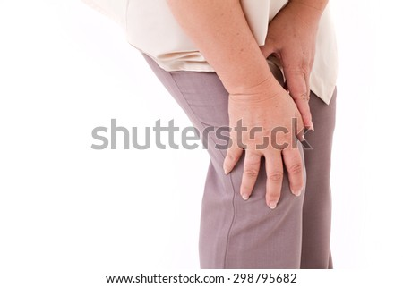 middle aged woman suffering from knee pain, joint injury or arthritis, hand holding knee