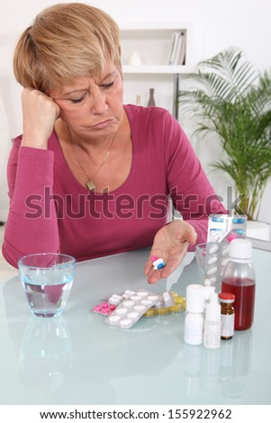 Middle-aged woman taking her medication - stock photo