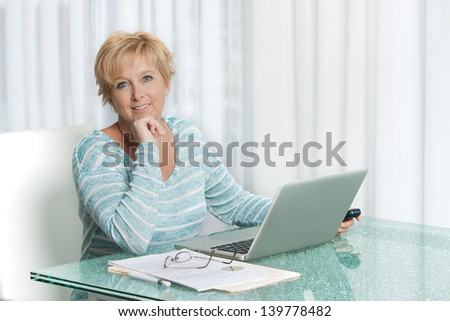 Middle aged woman talking on phone and working on a laptop from home ,pen in hand.