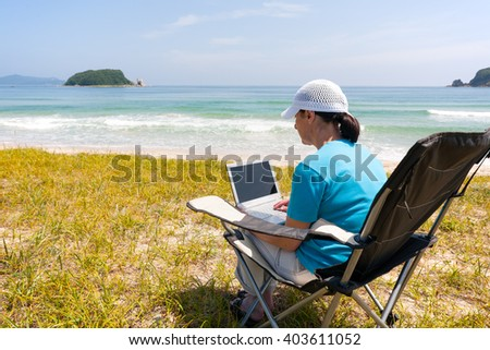 Middle-aged woman uses a laptop while on the beach on a summer day