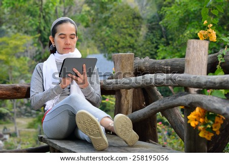 Middle aged woman using tablet computer in the park - stock photo