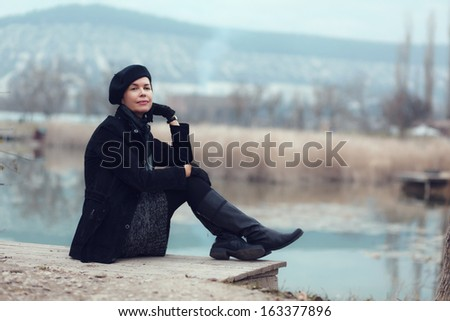 Middle aged woman walking in autumn park looking away