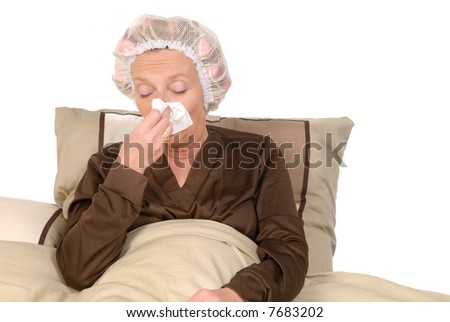 Middle aged woman with cold, sick in bed, blowing her nose.  Curlers and net in hair.