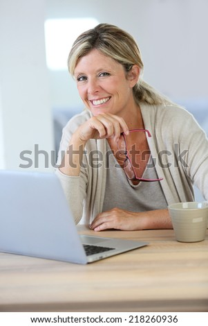 Middle-aged woman working on laptop at home