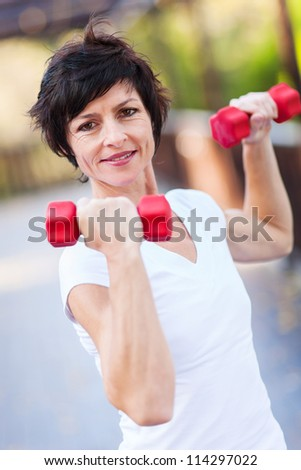 middle aged woman workout with dumbbells - stock photo