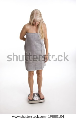 Middle-aged woman wrapped in towel standing on scale isolated against white background - stock photo