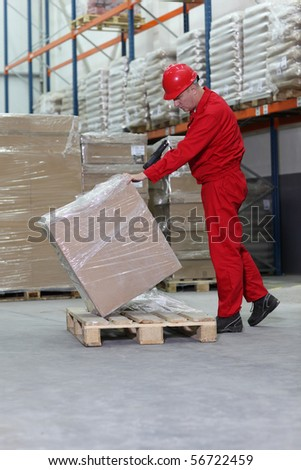 Middle aged workman in hard hat lifting cellophane wrapped box on wooden pallet in warehouse, stacked goods in background. - stock photo