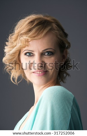 Middle-aged 40 year old woman glamor portrait of a gray background. - stock photo