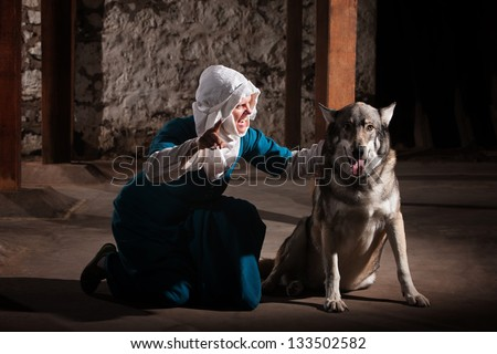 Middle ages nun dog owner talking to her pet - stock photo
