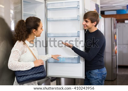 Middle class family couple choosing new refrigerator in hypermarket  - stock photo